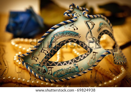 Ornate carnival mask on a music paper with rose and pearl - stock photo