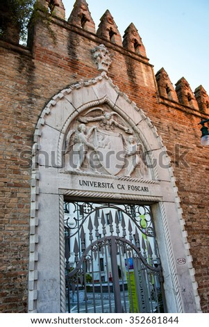 Ornate entrance gate to Venice University at Ca Foscari with a stone carved Gothic arch surrounding a wrought iron gate, Venice, Italy - stock photo