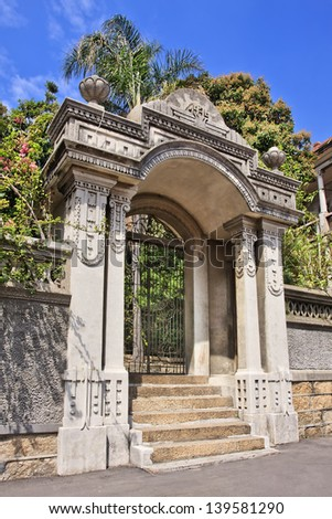 Ornate gate with ironwork and lush garden - stock photo