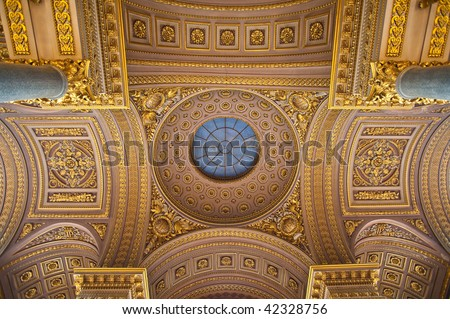 Ornate gilded gold ceiling details at the palace of Versailles. Fancy filigree and marble columns adorn the overhead arches. - stock photo