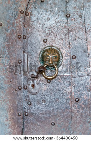 Ornate handle and door knocker on a medieval Benedictine church door - stock photo