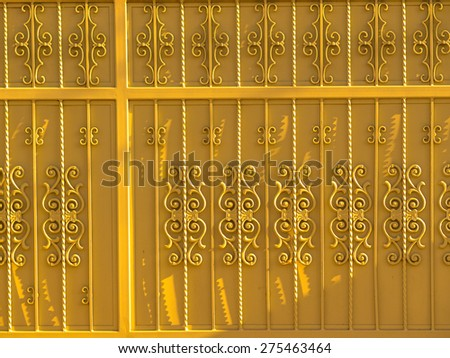 Ornate metal gate background, painted yellow. - stock photo