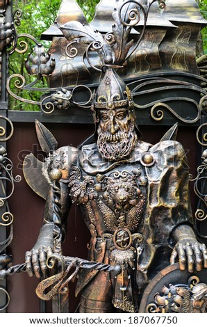 Ornate metal statue of a knight at arms wearing armour decorated with a lions head and dragon outdoors in a park or garden