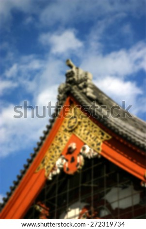 Ornate roof work with gold Buddhist symbol. Tokyo.  (Blur style image) - stock photo