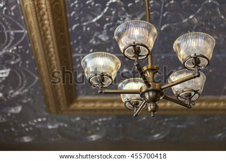 Ornate silver ceiling and lighting fixture, shallow depth of field with focus on light. - stock photo