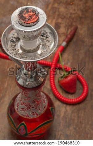 Ornate Syrian sheesha or hooka water pipe on wood table - stock photo