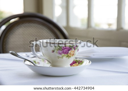 ornate tea cup with roses on a table, shallow focus - stock photo