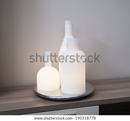 Ornate trio bottle light with tray on wooden shelf in living room