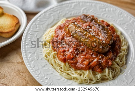 Ornate white plate with spaghetti, Italian sausage and marinara with a side of garlic bread.  - stock photo