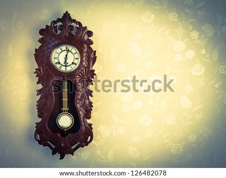 Ornate Wood Wallclock on Wall with Floral Wallpaper, Cross Processed Tones, and Copy Space. - stock photo