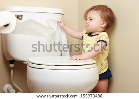Ornery baby pulling toilet paper off the roll - stock photo