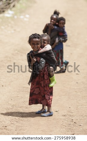 OROMIA, ETHIOPIA-APRIL 20, 2015: Unidentified child carries her sibling on her back in a small village in Ethiopia - stock photo