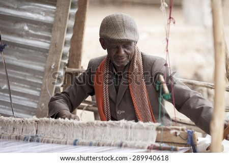 OROMIA, ETHIOPIA-APRIL 22, 2015: Unidentified man makes cloth on a loom in Ethiopia. There is also video of the same man making cloth.