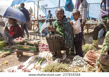 OROMIA, ETHIOPIA- NOVEMBER 5, 2014: Unidentified vegetable seller and her daughter sell their wares in open market in Ethiopia - stock photo