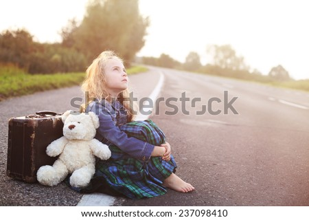 Orphan sits alone on the road with a suitcase - stock photo