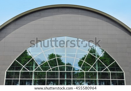 Orsha, Belarus - July 16, 2016: Sport Complex. Detail of the facade of circular shape of modern building. The design of arched roof and wall with glass and sandwich panels. - stock photo