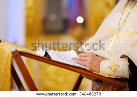 Orthodox christian priest reading church book   - stock photo