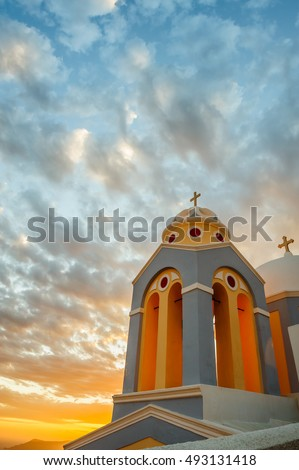 Orthodox church in rays of beautiful sunset. Fira, Santorini Greece. Copyspace