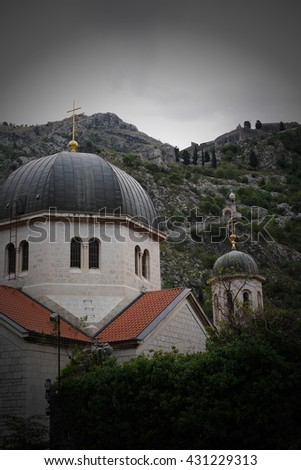 Orthodox church roof in front of rock hills, very cloudy day, Kotor, Montenegro, Eastern Europe