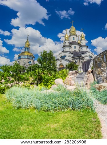 Orthodox church with a separate bell tower with a lawn and ornamental shrubs in the foreground against the sky with clouds