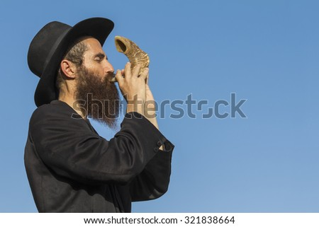 Orthodox Jewish man blast in Shofar at Rosh Hashana holiday on blue sky background - stock photo