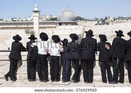Orthodox Jews stand in front of the Western Wall. - stock photo
