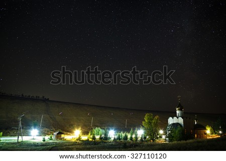 Orthodox Monastery on the background of stars in the night sky. - stock photo