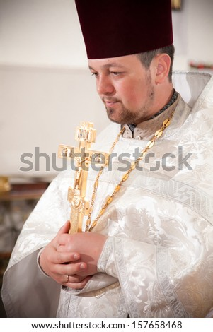 Orthodox priest holding candles - stock photo