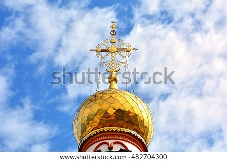 Orthodox (Russian) cross on  a church dome (cupola) against cloudy blue sky - Cathedral of the Epiphany, Irkutsk, Siberia, Russia