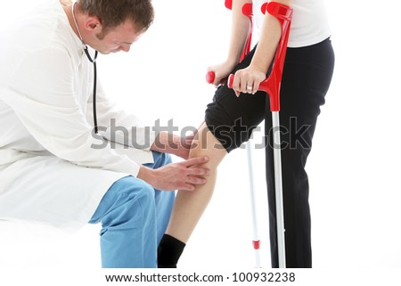 Orthopaedic surgeon examining woman's knee Orthopaedic surgeon sitting examining the knee of a female patient on crutches following surgery for a joint injury - stock photo