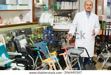 Orthopaedist posing near display with orthopaedic equipment and machines