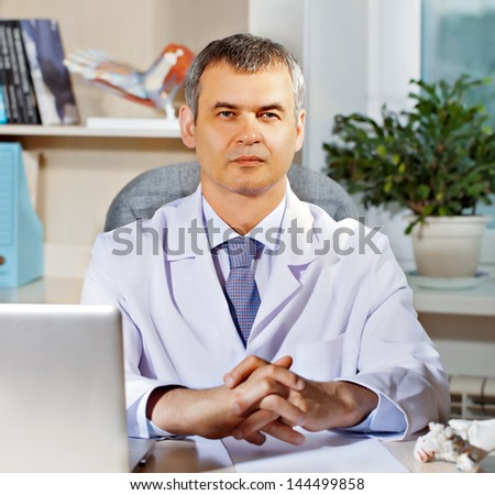 Orthopedic doctor in his office with the model of the feet - stock photo