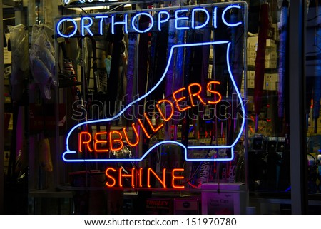 Orthopedic shoes neon sign in a Manhattan shoe repair store window - stock photo