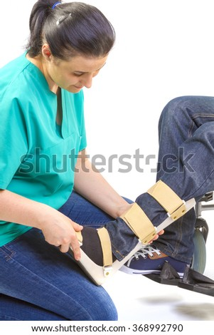 Orthopedist puts orthosis to patient in wheelchair with disabilities - stock photo