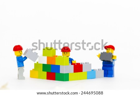 Orvieto, Italy - January 16th 2015: team of workman Lego mini figure build a wall. Lego is a popular line of construction toys manufactured by the Lego Group - stock photo