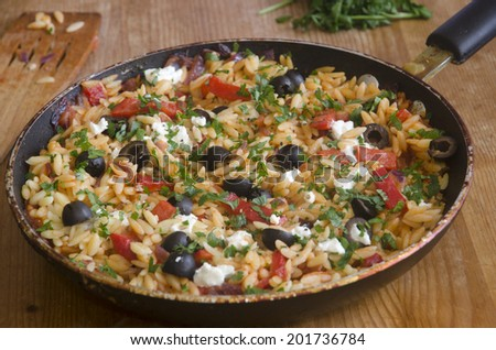 Orzo with peppers, olives and goat's cheese - stock photo