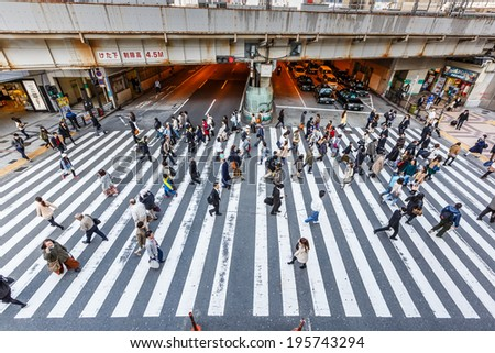 OSAKA - APR 7: People walk across the street  at Osaka station on Apr 7,14 in Osaka. It is a city in the Kansai region of Japan's main island of Honshu, a designated city under the Local Autonomy Law. - stock photo