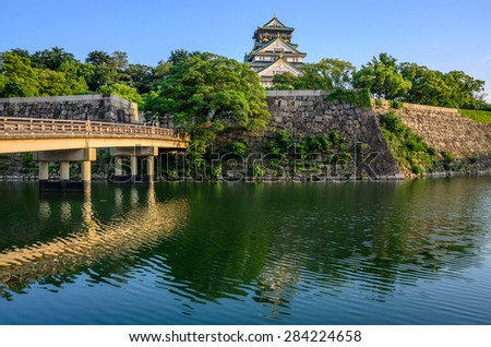 Osaka Castle and bridge that spans the moat. The castles basks in the warm light of the late afternoon sun in Osaka, Japan.