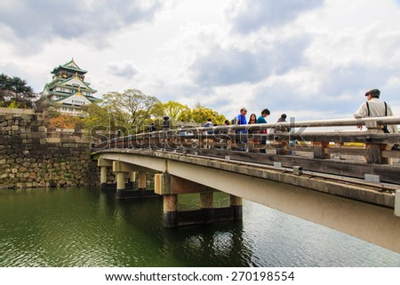 OSAKA, JAPAN- APR 12: Tourists visit Osaka castle in Osaka city, Japan on April 12, 2015. The castle is one of Japan most famous and it played a major role in the unification of Japan. - stock photo