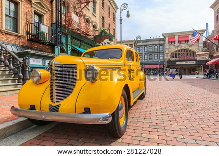Osaka, Japan - Apr 9:View yellow cap car on street  vintage building at  Universal Studios Theme Park in Osaka, Japan on Apr 9, 2015.  - stock photo