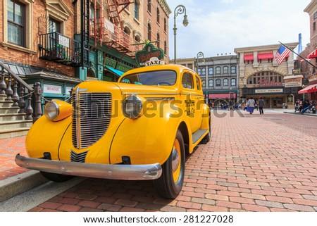 Osaka, Japan - Apr 9:View yellow cap car on street  vintage building at  Universal Studios Theme Park in Osaka, Japan on Apr 9, 2015.  - stock photo