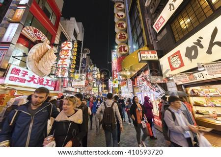 OSAKA, JAPAN - APRIL 13, 2016: Tourists walking around pedestrian walking street at Dotonbori arcade under the iconic oversized octopus and night light signs in Namba district of Osaka, Japan - stock photo