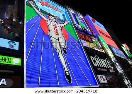 OSAKA JAPAN - 19 JUNE, 2014: Glico sign in Dotonbori entertainment district. Dotonbori is one of the principal tourist destinations in Osaka  - stock photo