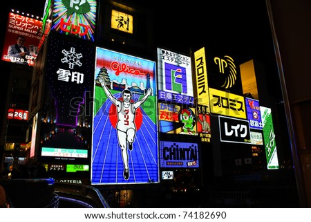 OSAKA, JAPAN - JUNE 29: The Glico Man Running billboard and other neon displays on June 29, 2010 in  Dotonbori, Osaka, Japan. Dotonbori has many shops, restaurants and colorful billboards.