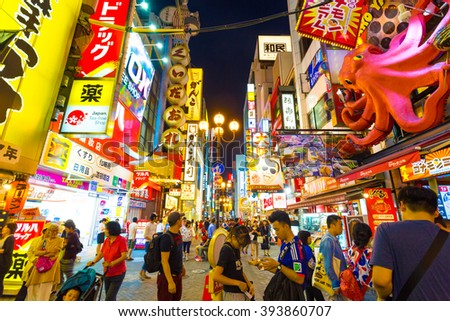 OSAKA, JAPAN - JUNE 23, 2015: Tourists around pedestrian walking street at Dotonbori arcade under the iconic oversized octopus and night light signs in Namba district