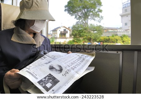 OSAKA, JAPAN-NOVEMBER 6, 2014; lady with mouth mask in Japanese train reading a newspaper. November 6, 2014 Osaka, Japan - stock photo