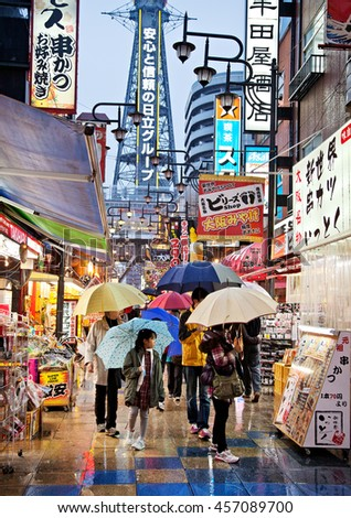 """OSAKA, JAPAN - OCTOBER 31: The district of Shinsekai (""""New World"""" in English) and Tsutenkaku Tower on a rainy winters evening on October 31, 2010 in Osaka, Japan. The tower was constructed in 1912. - stock photo"""