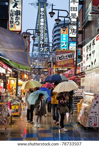 "OSAKA, JAPAN - OCTOBER 31: The district of Shinsekai (""New World"" in English) and Tsutenkaku Tower on a rainy winters evening on October 31, 2010 in Osaka, Japan. The tower was constructed in 1912. - stock photo"