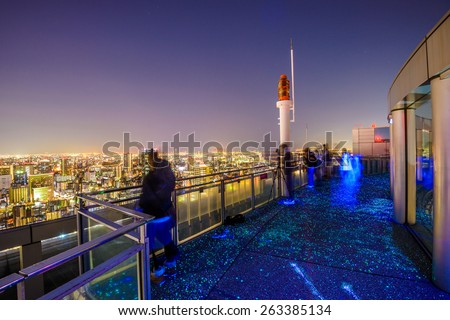 OSAKA, JAPN - NOVEMBER 24, 2012: Tourists enjoy the skyline view from the Floating Garden Observatory on the Umeda Sky Building at night. - stock photo