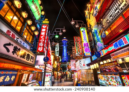 OSAKA - NOVEMBER 24: Tsutenkaku Tower in Shinsekai (new world) district at night on November 24, 2014, in Osaka. It is a tower and well-known landmark of Osaka, Japan and advertises Hitachi. - stock photo